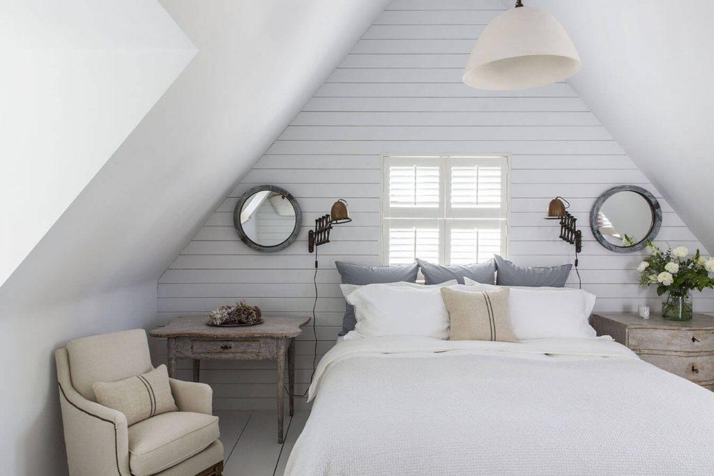 C'est la chambre avec un lit et un fauteuil devant une table de nuit