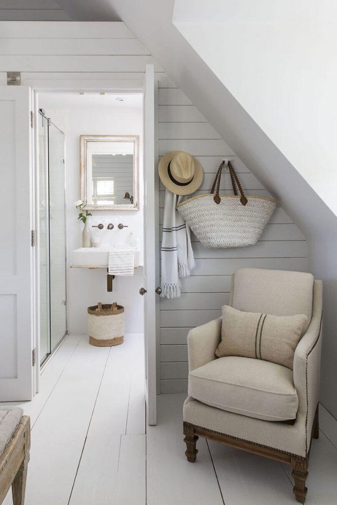 La salle de bain est située à gauche de la photo et le fauteuil est à droite de la photo dans le couloir