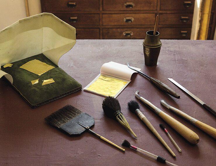 Un coussin, une palette à dorer, couteau, pinceaux et brunissoirs sont posés sur une table pour redorer
