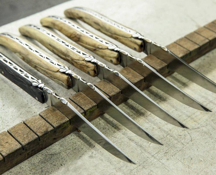 5 couteaux pliants en bois posés sur une planche en bois