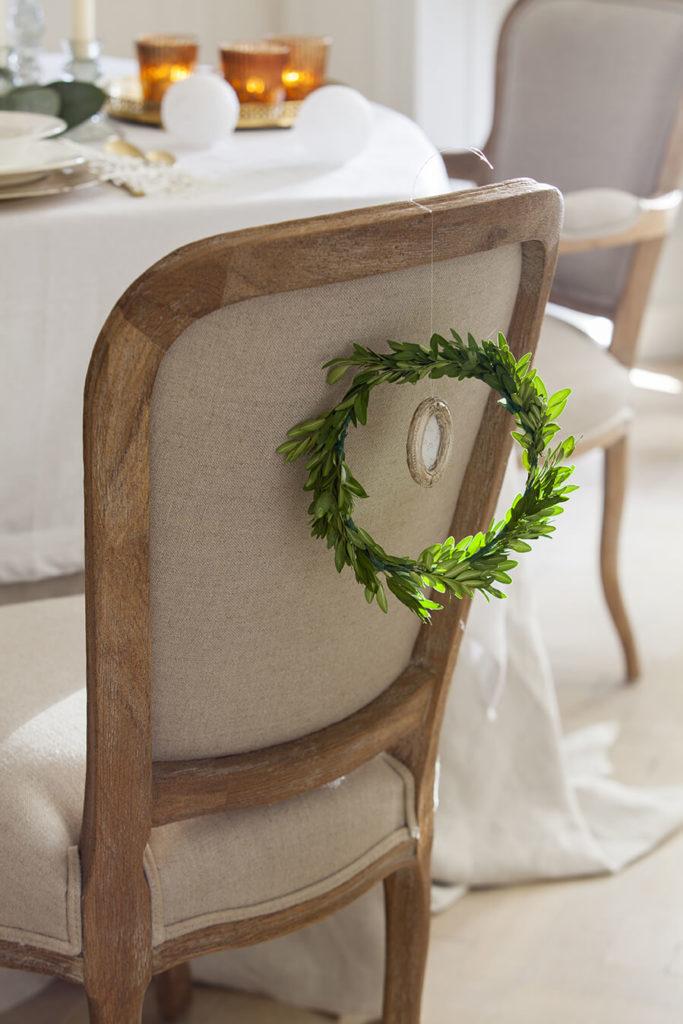 Une couronne de branches d'eucalyptus suspendues sur une chaise pour une déco de noël