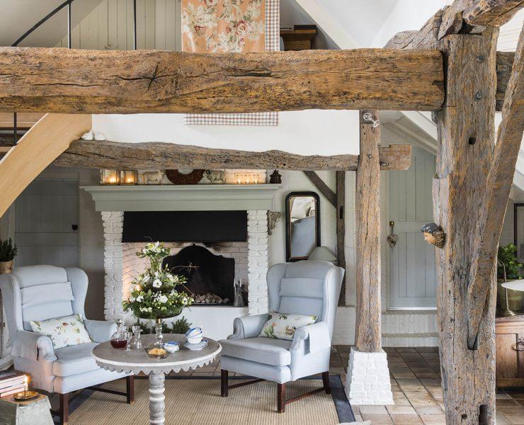 Intérieur d'une maison de campagne avec poutre en bois et deux fauteuils gris autour d'une petite table ronde