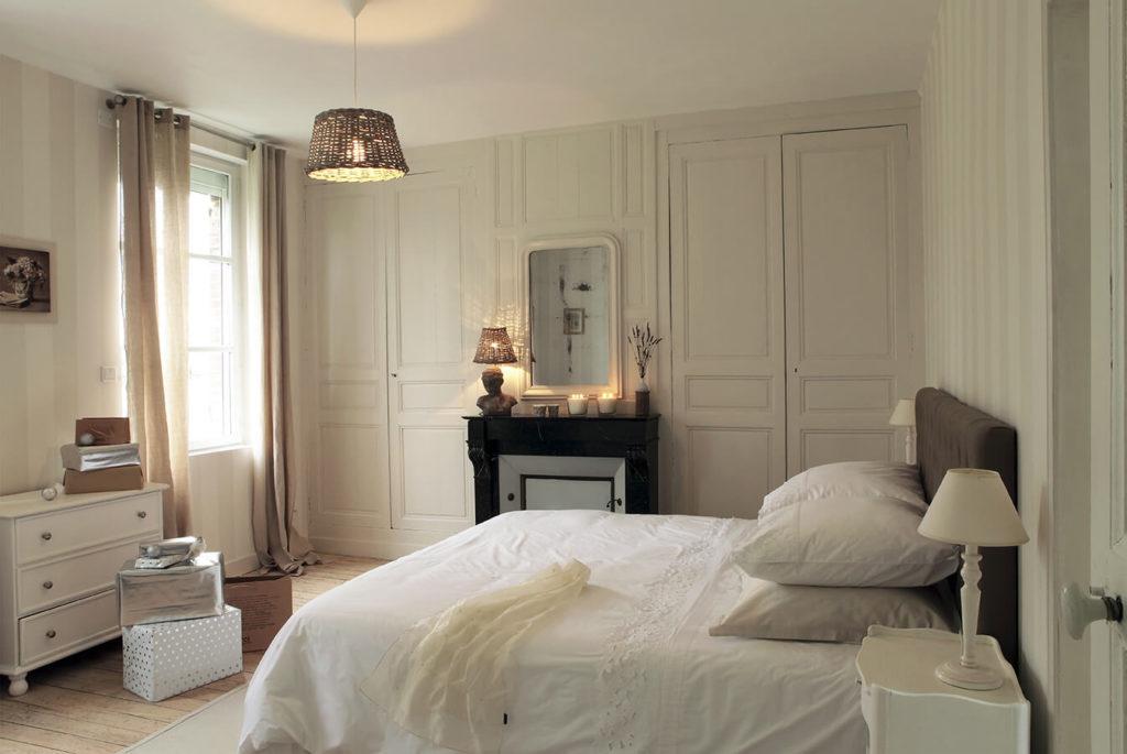 Chambre avec grand lit et commode repeinte en blanc
