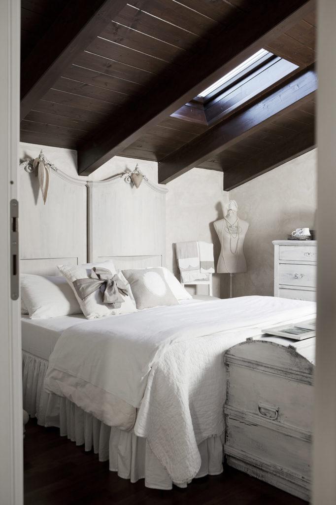 Chambre avec lit deux places et poutres en bois à la déco noel shabby