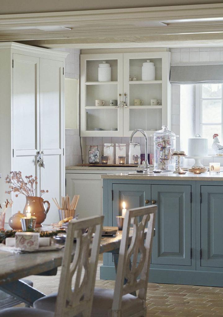 Cuisine avec meuble bleu et des bougies sur la table pour une ambiance noel rustique chic
