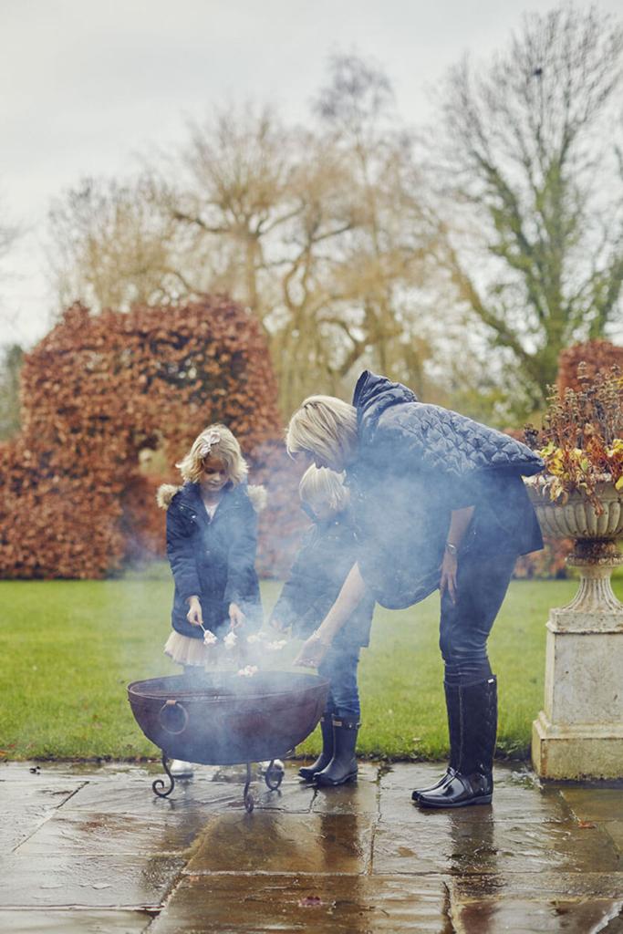 Une femme et ses deux enfants grillent de la guimauve pour noel