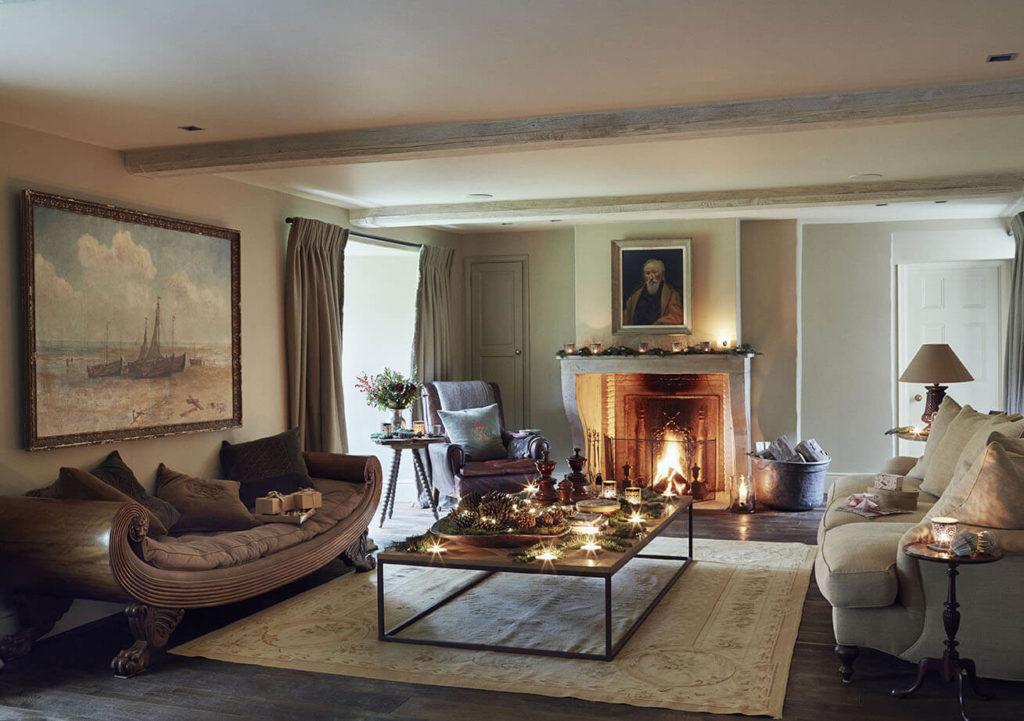 Salon avec grand canapé et coussins dessus avec une petite table au centre et des bougies pour une ambiance noel rustique chic