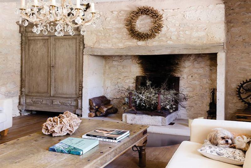 Cheminée authentique avec couronne en bois flotté au-dessus dans une maison de campagne à l'interieur rustique chic