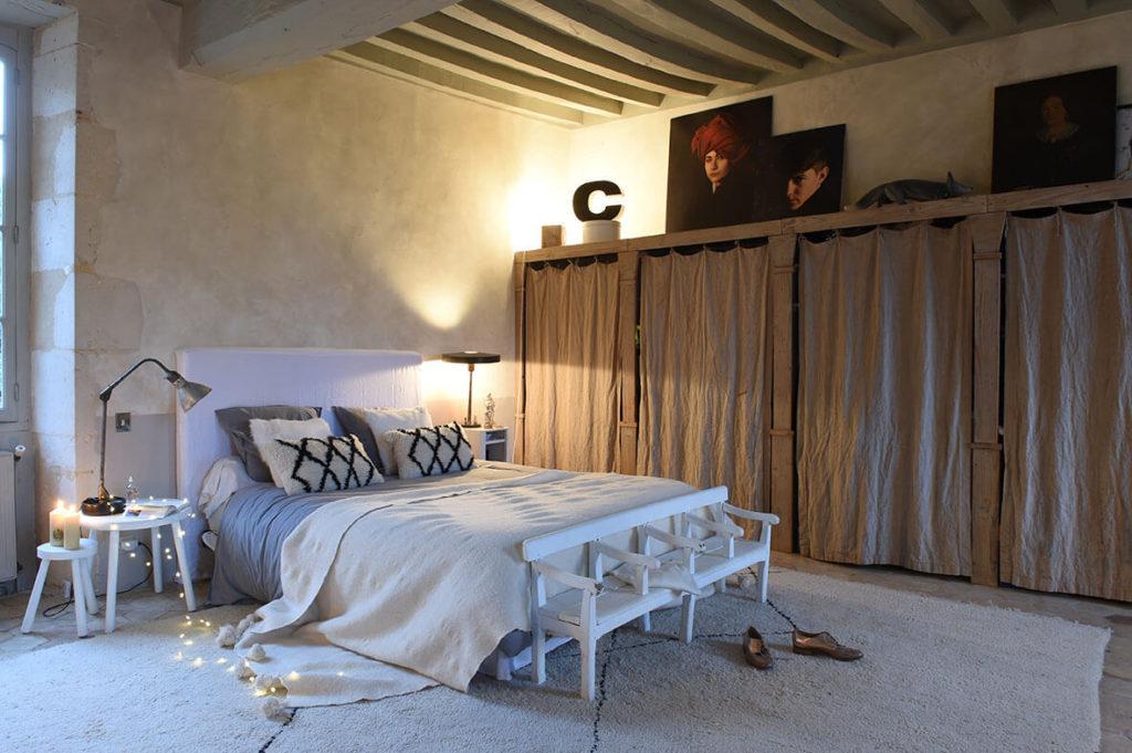 Chambre aux teintes natures relevées de touche sombres avec un lit au centre