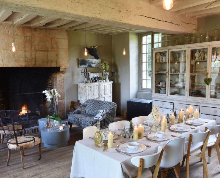 Salon décoré pour Noël avec une table à manger et des bougies lumineuses par dessus
