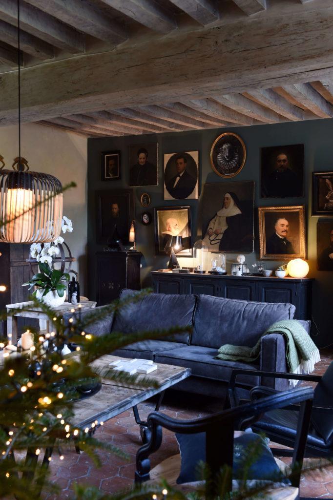 Un canapé bleu avec un sapin de Noël décoré de guirlande