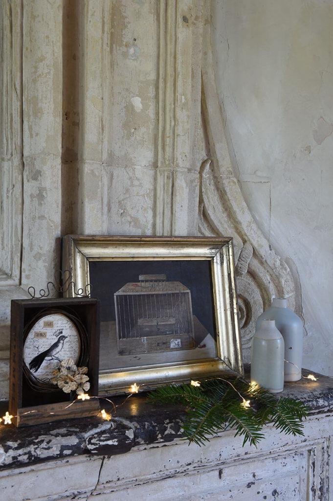 Au dessus de la cheminé, une petite huile et des guirlandes lumineuses pour décorer l'intérieur