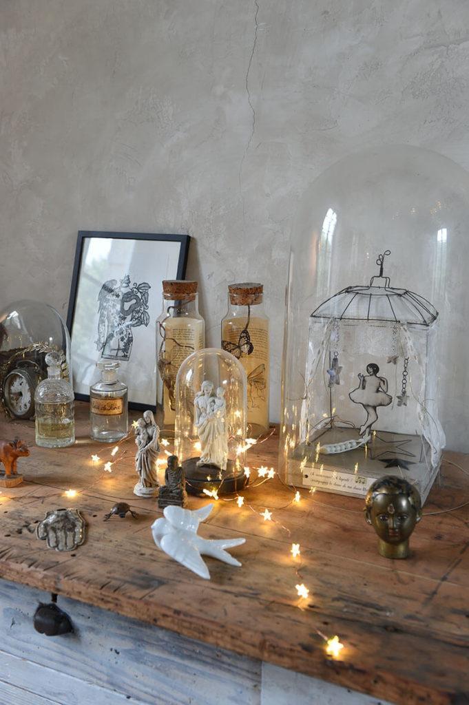 Objets chinés posés sur une table avec des guirlands lumineuse afin de décorer l'intérieur