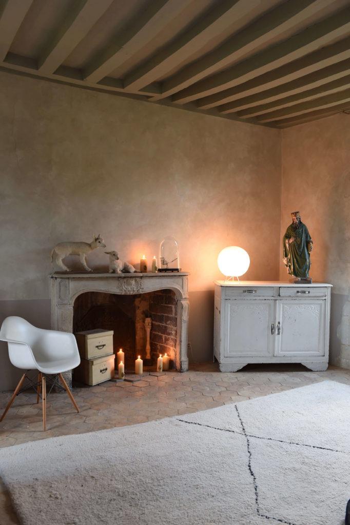 Chambre à la déco minimaliste, avec une petite commode, une cheminé et une table