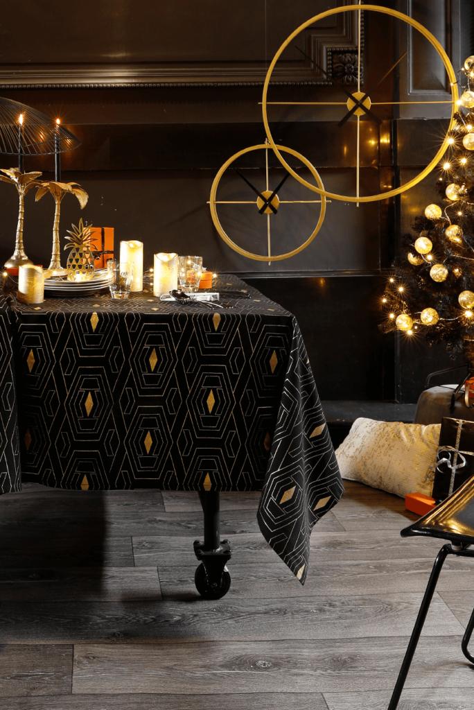 Nappe de fête en noir et or, motifs dorés, 100% coton, à partir de 49,90€ ; Becquet.