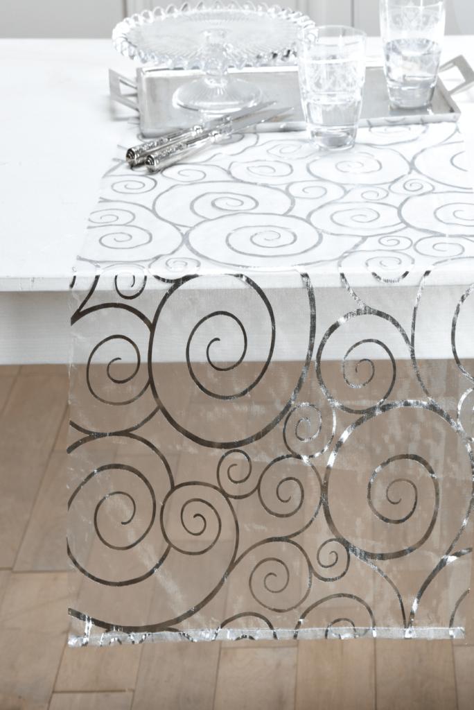 Nappe de fête motifs spirales argentées, 100% polyester transparent, elle se pose à même la table ou sur une nappe textile unie, finition par ourlet ; Becquet.