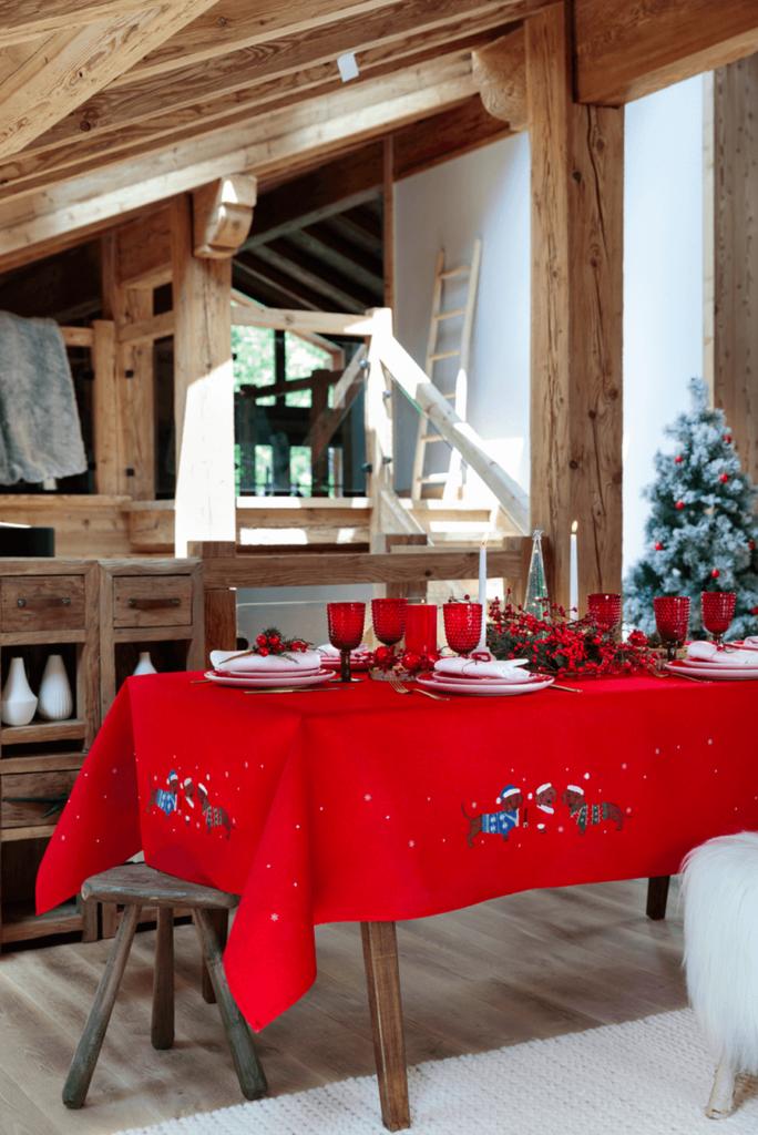 Nappe rouge brodée de petits chiens déguisés en père noël, disponible en carré, rectangulaire, à partir de 65,00€ ; Linvosges.