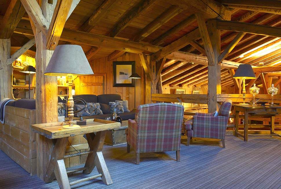 Petit salon avec chaises et canapé dans un chalet en bois