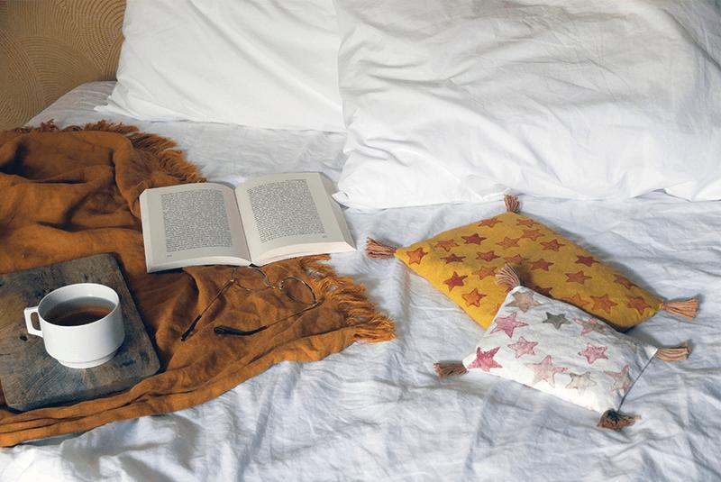 Coussins jaune et blanc sur un lit crées à partir du tuto housse de coussin