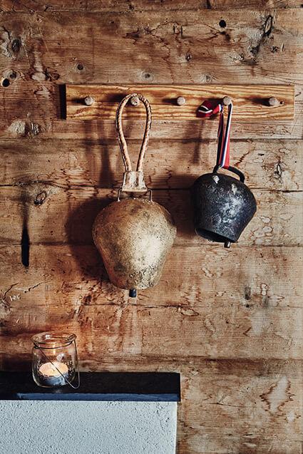 Paire de cloche sur un mur en bois dans un chalet à la déco ethnique chic