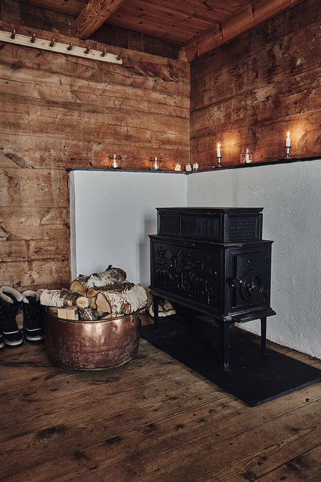 Grande poêle à bois en fonte noire dans une petit cabane au style ethnique chic